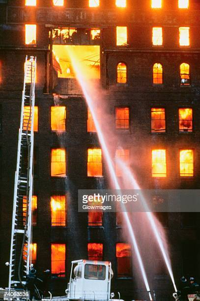 Fire fighters spraying water at a burning factory, Baltimore, Maryland, USA
