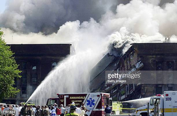 Fire fighters struggle to contain a spreading fire after a highjacked commercial jetliner crashed into the Pentagon September 11 2001 in Arlington...