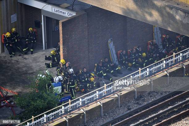 Fire fighters take a rest near the building after a huge fire engulfed the 24 storey residential Grenfell Tower block in Latimer Road West London in...