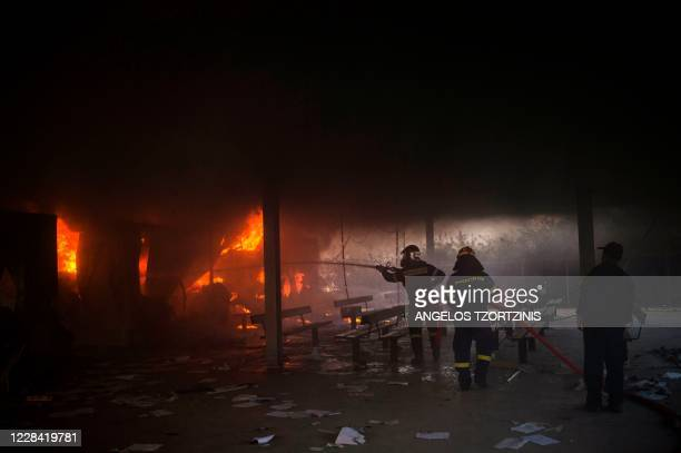 Fire fighters try to extinguish a blaze with a hose in the camp of Moria on the island of Lesbos after a major fire broke out, on September 9, 2020....