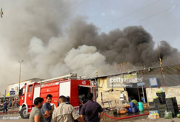 Fire fighters try to extinguish a fire after a suicide bomber blew himself up near a market place at al Jadeed district of Baghdad Iraq on April 25...