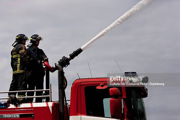 Fire fighters using hose on truck