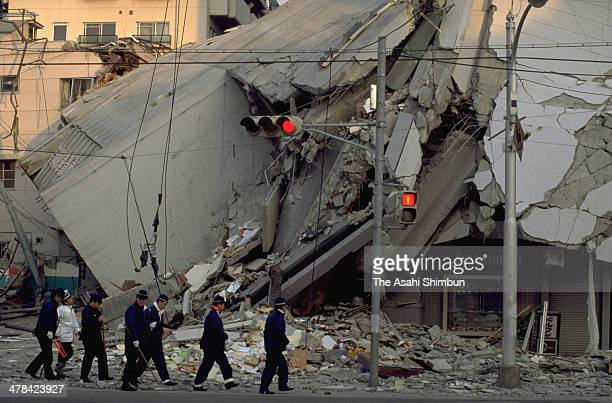 Fire fighters walk around collapsed buildings after the Great Hanshin earthquake on January 18 1995 in Kobe Hyogo Japan Magnitude 73 strong...