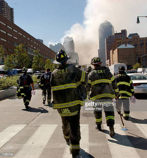 Fire fighters walk towards the World Trade Center September 12 2001 in New York City one day after the twin towers were attacked and destroyed by...