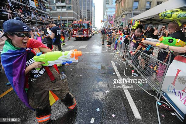 TORONTO ON JULY 3 Fire fighters water fight members of the crowd during the the 2016 Toronto Pride parade along Yonge Street in Toronto July 3 2016
