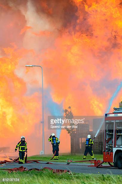 "fire fighters with huge flames in the bakcground - ""sjoerd van der wal"" imagens e fotografias de stock"