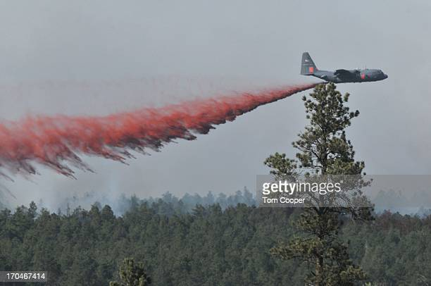 A fire fighting aircraft dumps fire retardent over a fire that's been burning since Tuesday near Colorado Springs June 13 2013 in Black Forest...