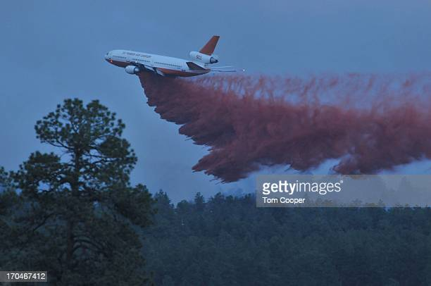 A fire fighting aircraft empties fire retardent over a fire that's been burning since Tuesday near Colorado Springs June 13 2013 in Black Forest...