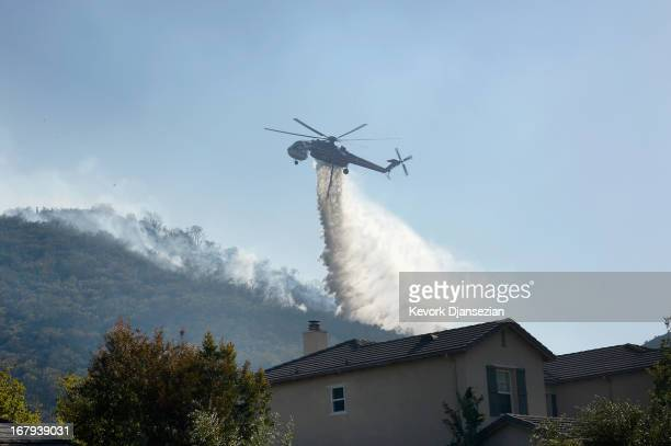 Fire fighting helicopters make water drops onto a hillsdie behind homes threatened by the out of control wildfire on May 2 2013 in Newbury Park...