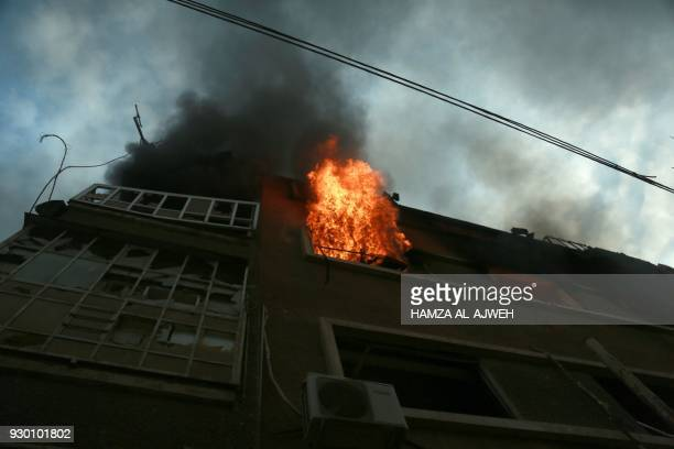 Fire flames rip through a building following Syrian government bombardment in the town of Douma in the rebelheld enclave of Eastern Ghouta on the...