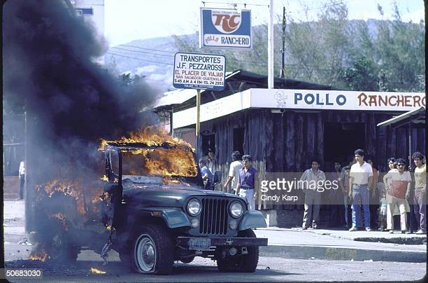 Fire flaming from military vehicle set afire by students workers peasants who are protesting assassination of Human Rights Comm president Herbert...