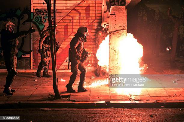 TOPSHOT Fire from a molotov cocktail rises near Greek riot police during clashes around the Polytechnic school following a protest against the visit...