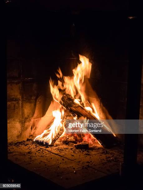 a fire glows in a log burning stove in norway, summertime - 暖炉の火 ストックフォトと画像