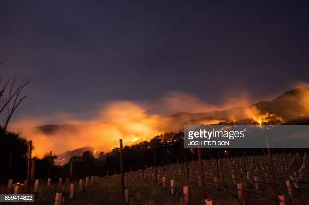 Fire glows on a hillside in Napa California on October 9 as multiple winddriven fires continue to whip through the region