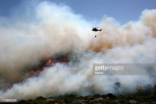 Fire helicopter extinguishes a fire with a fire bucket