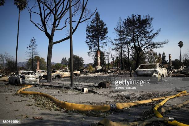 A fire hose lays in the street in front of homes that were destroyed by the Tubbs Fire on October 12 2017 in Santa Rosa California Twenty four people...