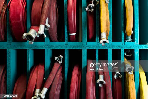 fire hoses placed on shelves - cog stock pictures, royalty-free photos & images
