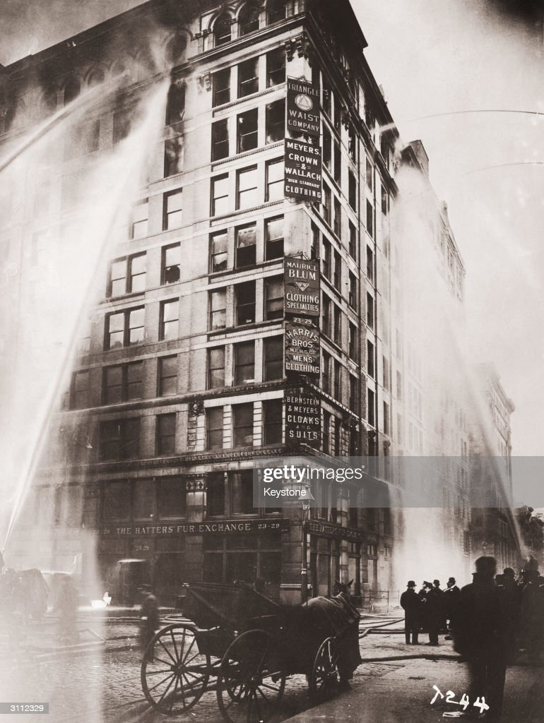 Fire hoses spray water on the upper floors of the Asch Building (housing the Triangle Shirtwaist Company) on Washington and Greene Streets, during the fire in New York City, March 25, 1911.