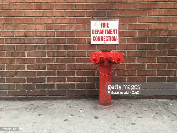 Fire Hydrant By Sign Board On Brick Wall