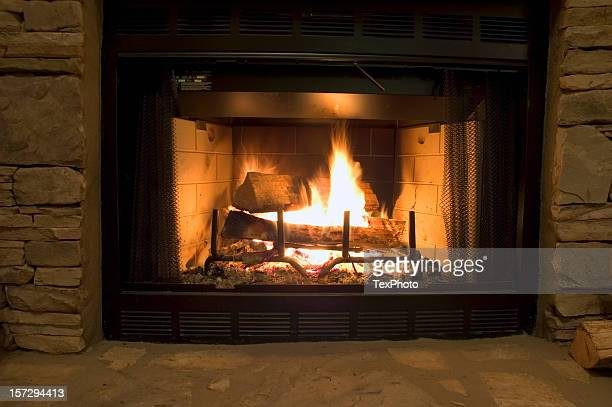 Fire in a fireplace by stone wall