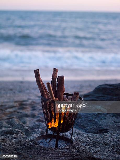 Fire in camping stove on beach at dusk