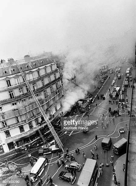 Fire in the Monoprix store of the Avenue de L'Opéra with dozens of firemen fighting in Paris France circa 1960