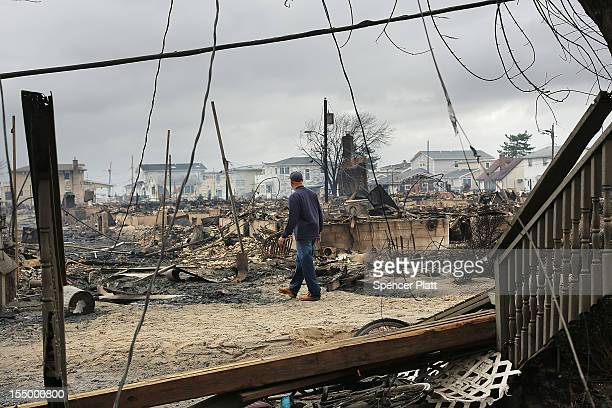 Fire inspector walks through a neighborhood destroyed during Hurricane Sandy October 30, 2012 in the Breezy Point neighborhood of the Queens borough...