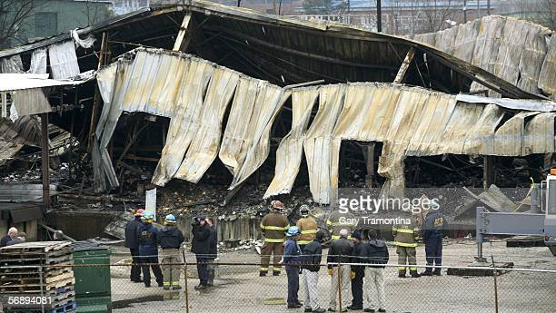 Fire investigators and firefighters survey a damaged warehouse owned by Multi Marketing Inc February 20 2006 in Tuscaloosa Alabama The building which...