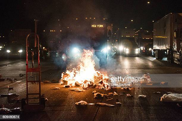 A fire lit by protesters burns in front of a bus on the I85 during protests in the early hours of September 21 2016 in Charlotte North Carolina The...