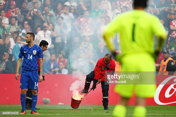 Fire marshal reacts after fireworks are thrown onto the pitch during the UEFA EURO 2016 Group D match between Czech Republic and Croatia at Stade...