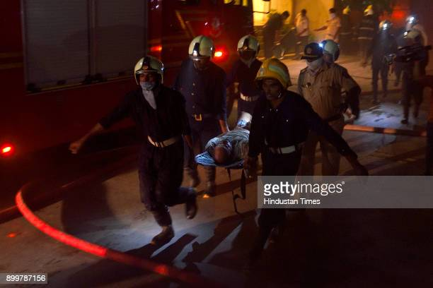 Fire men rush to ambulance to rescued victims after the massive fire at restaurant in Kamala Mill Compound Lower Parel on December 29 2017 in Mumbai...