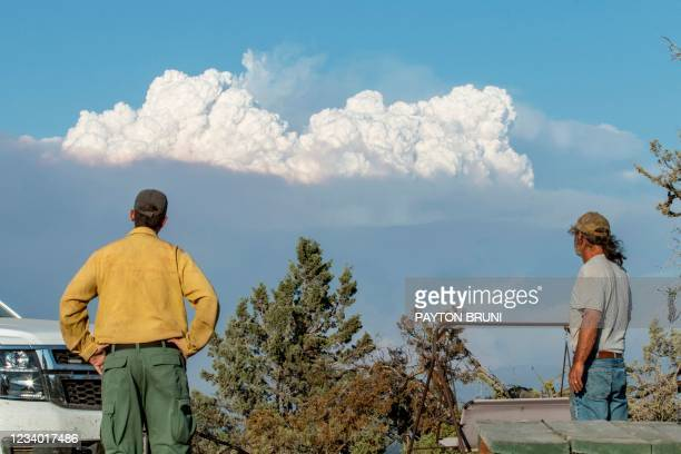 Fire Mitigation and Education Specialist Ryan Berlin and home owner Bob Dillon watch the Bootleg Fire smoke cloud from Dillon's home in Beatty,...