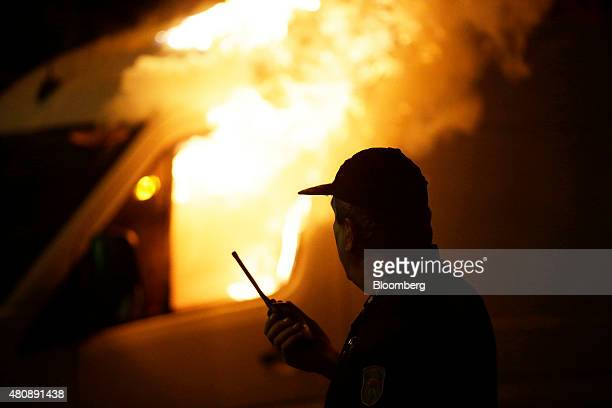 A fire officer attends to a burning television broadcast vehicle set on fire by antibailout protestors during a demonstration outside the Greek...