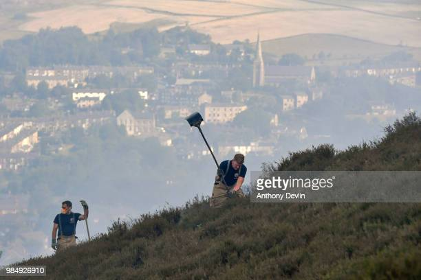 Fire officers use beaters to fight a large wildfire on the moors above Stalybridge Greater Manchester on June 27 2018 in Stalybridge England...
