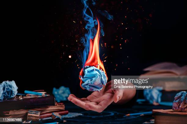 fire on a crumpled paper ball in a writer workplace with drafts, papers, books, and pencils. creative block concept. dark background with copy space - the_writer's_block stock pictures, royalty-free photos & images