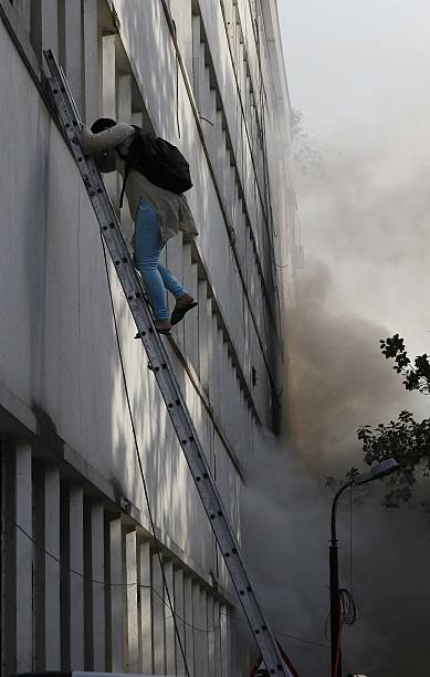 Fire personnel helping a man evacuate after a major fire broke out in a four storey UCO Bank building housing Punjab National Bank at Parliament...