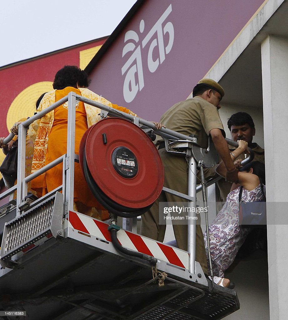 Fire personnel rescuing a woman after a major fire broke out in a four storey UCO Bank building housing Punjab National Bank at Parliament Street on..