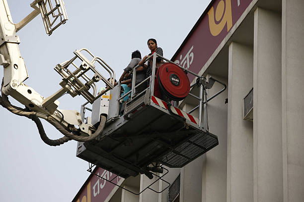 Fire personnel rescuing stranded people after a major fire broke out in a four storey UCO Bank building housing Punjab National Bank at Parliament...