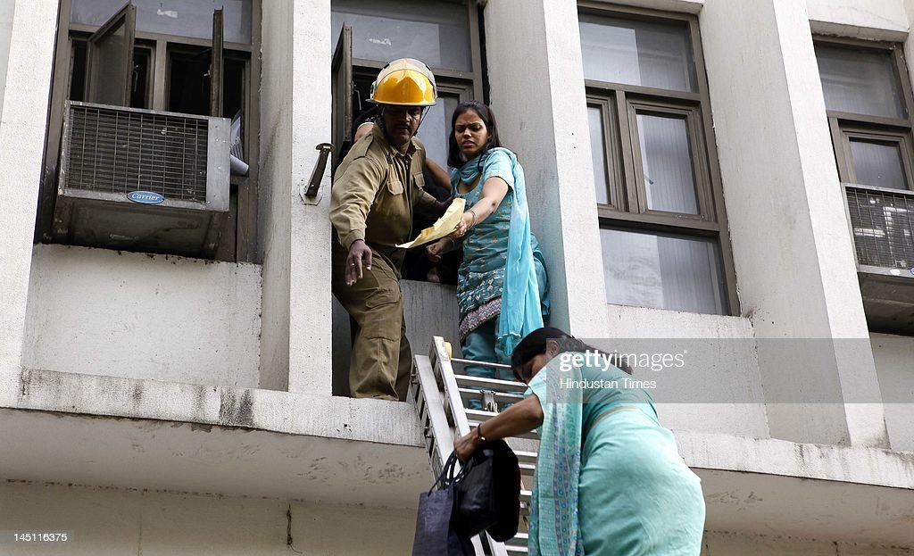 Fire personnel rescuing two women after a major fire broke out in a four storey UCO Bank building housing Punjab National Bank at Parliament Street...