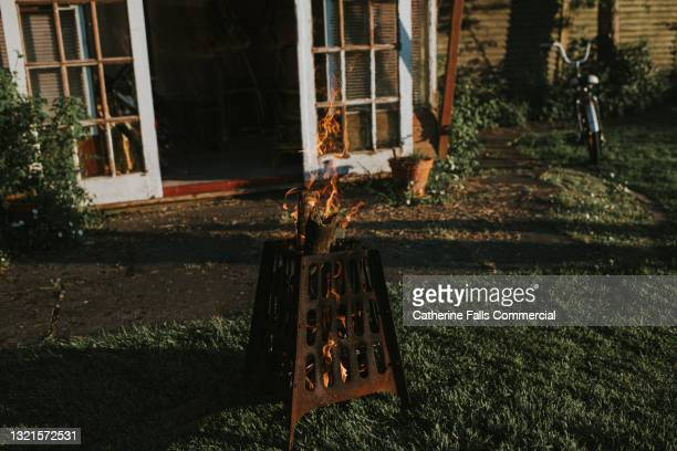 fire pit burning in a back garden at dusk, with space for copy - warming up stock pictures, royalty-free photos & images