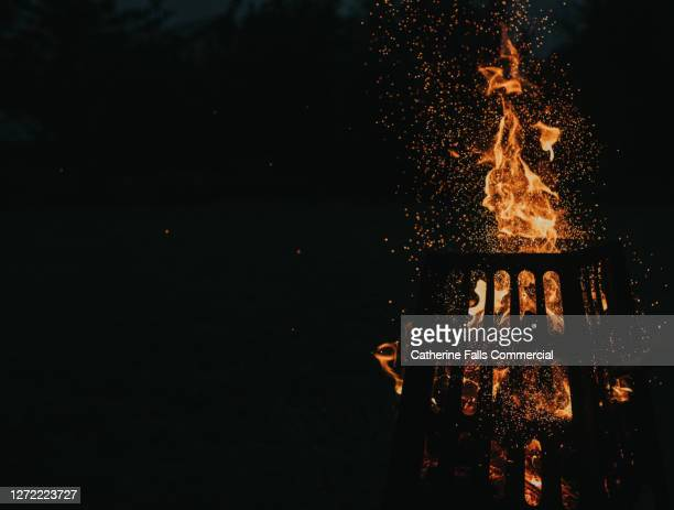 fire pit fiercely burning in the dark with space for copy - warming up stock pictures, royalty-free photos & images