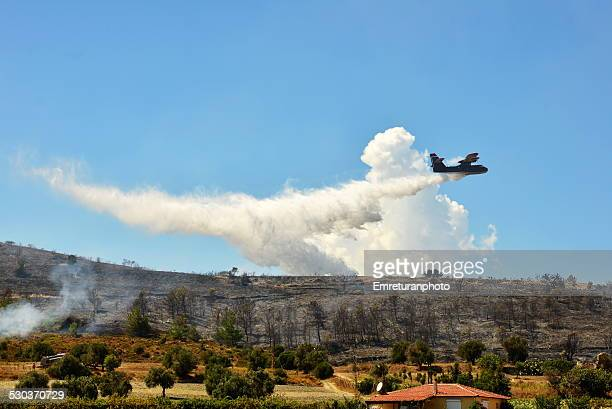 fire plane extinguishing a bush fire - emreturanphoto stock pictures, royalty-free photos & images