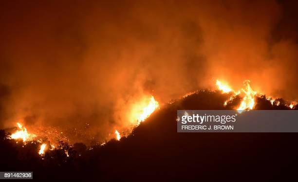 Fire rages across a Romero Canyon hillside in Montecito California north of Santa Barbara on December 12 2017 Crews battling wildfires ravaging...