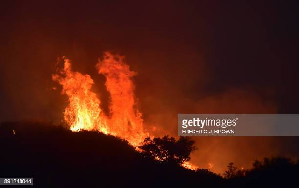 Fire rages along Romero Canypn hillsides in Montecito north of Santa Barbara California on December 12 2017 Crews battling wildfires ravaging...