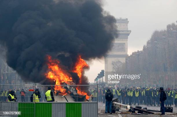 A fire rages as men wearing yellow vests protest against rising fuel prices on the ChampsElysees avenue on November 24 2018 in Paris France The...