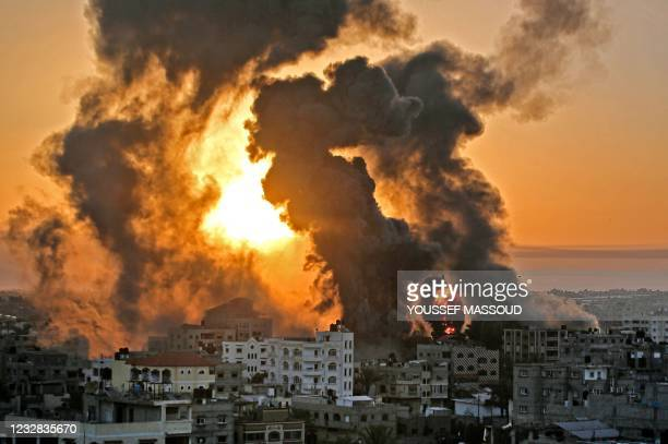 Fire rages at sunrise in Khan Yunish following an Israeli airstrike on targets in the southern Gaza strip, early on May 12, 2021. - Israeli air raids...