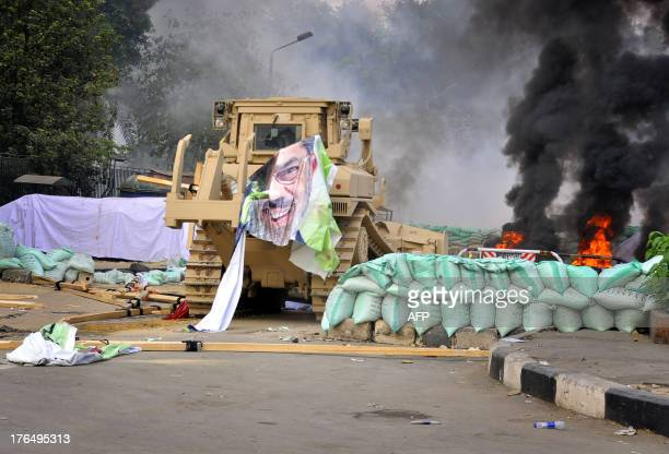 Fire rages in the background as an Egyptian military bulldozer dismantles the protest camp at Cairo's Al-Nahda square after security forces dispersed...