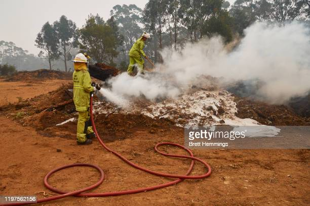 Fire Rescue Queensland crews work to put out smouldering fires on January 5, 2020 in Wingello, Australia. One person has died overnight in Batlow and...