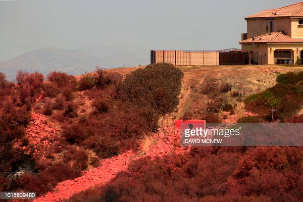 Fire retardant that was dropped by a firefighting jet to protect houses is seen over the canyon slope as some residents who were forced to flee the...