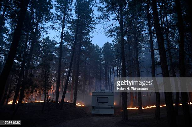 Fire runs along the bed of the forest near a camper off of Herring Road in the Black Forest northeast of Colorado Springs CO on June 11 2013 Many...